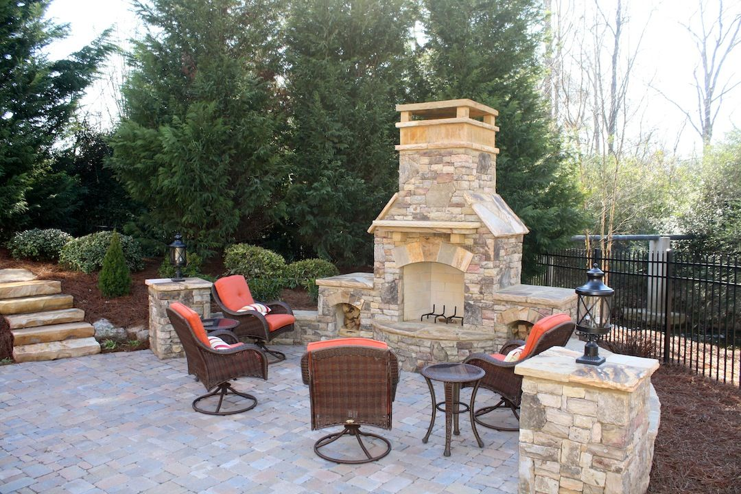 Outdoor Stacked Stone Fireplace With Seating Wall And Wood Box