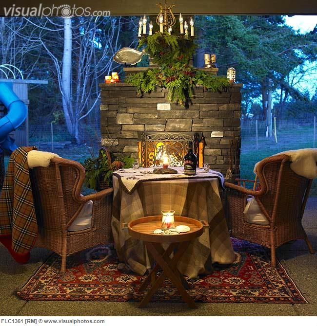 Outdoor fireplace on patio with two wicker chairs and