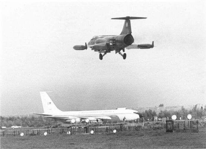 Een militaire Boeing 707 is geland op de vliegbasis te Leeuwarden met een aantal hoge gasten aan boord, waaronder de Amerikaanse viersterrengeneraal B. Poe. Daarboven een Lockheed F-104G Starfighter tijdens de landing. Keegsdijkje 04-10-1979 Joop Fenstra,  : fotograaf LC