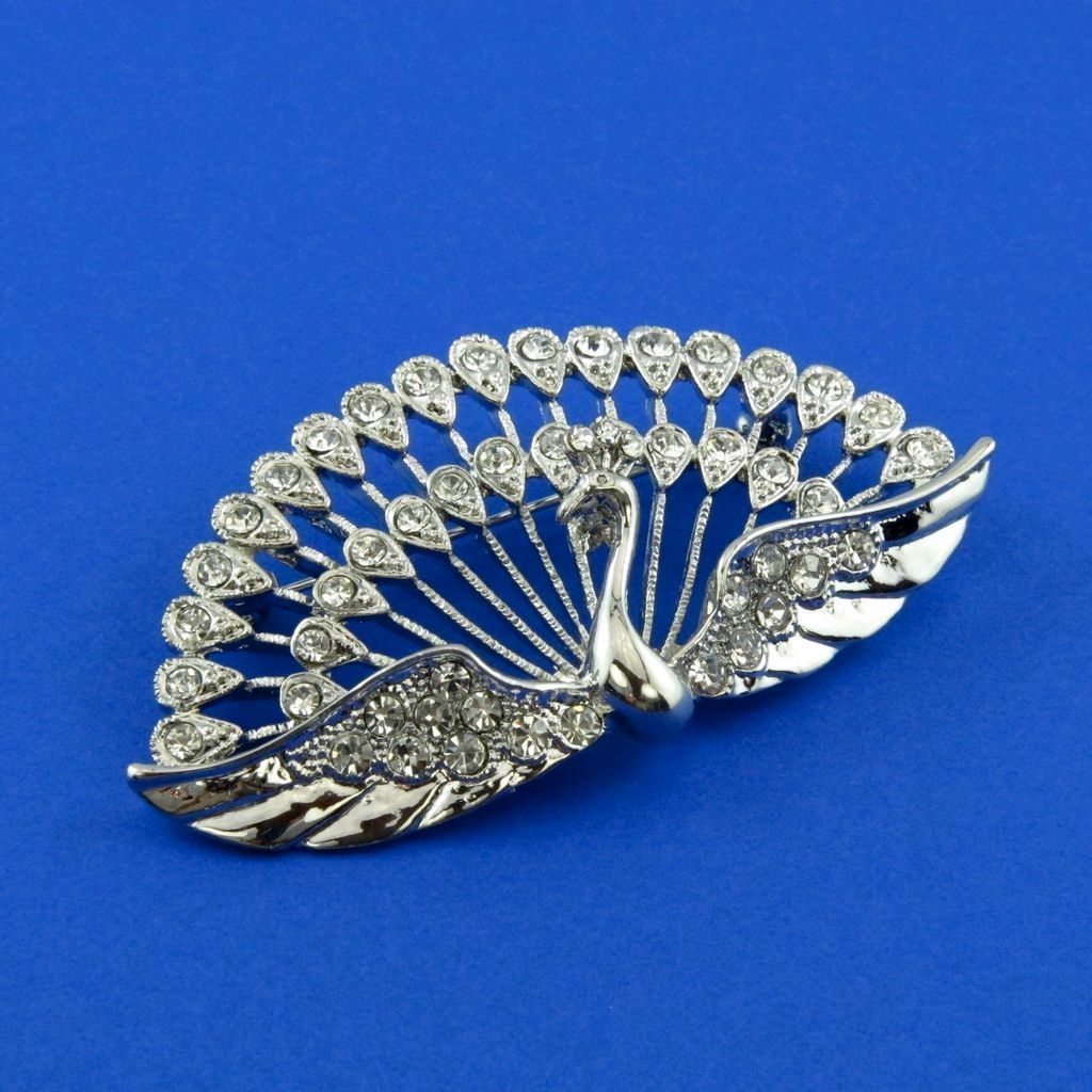 Simple in color, spectacular in presentation, this peacock is flaring a shining silver tone metal tail with sparkling clear rhinestone feathers. Resembling the brooches made in the 1940's of sterling silver (or rhodium plated) and clear rhinestones, this bird pin is the seasonal vintage spark that you need on that little black dress, sweater or suit lapel.