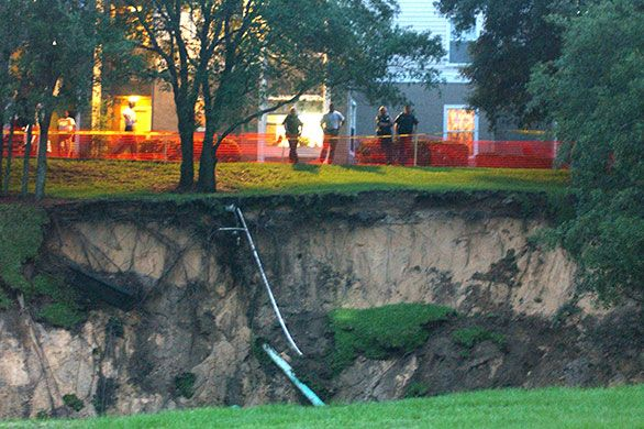 Sinkholes: 2002, Orlando, US: Emergency personnel stand by a giant sinkhole