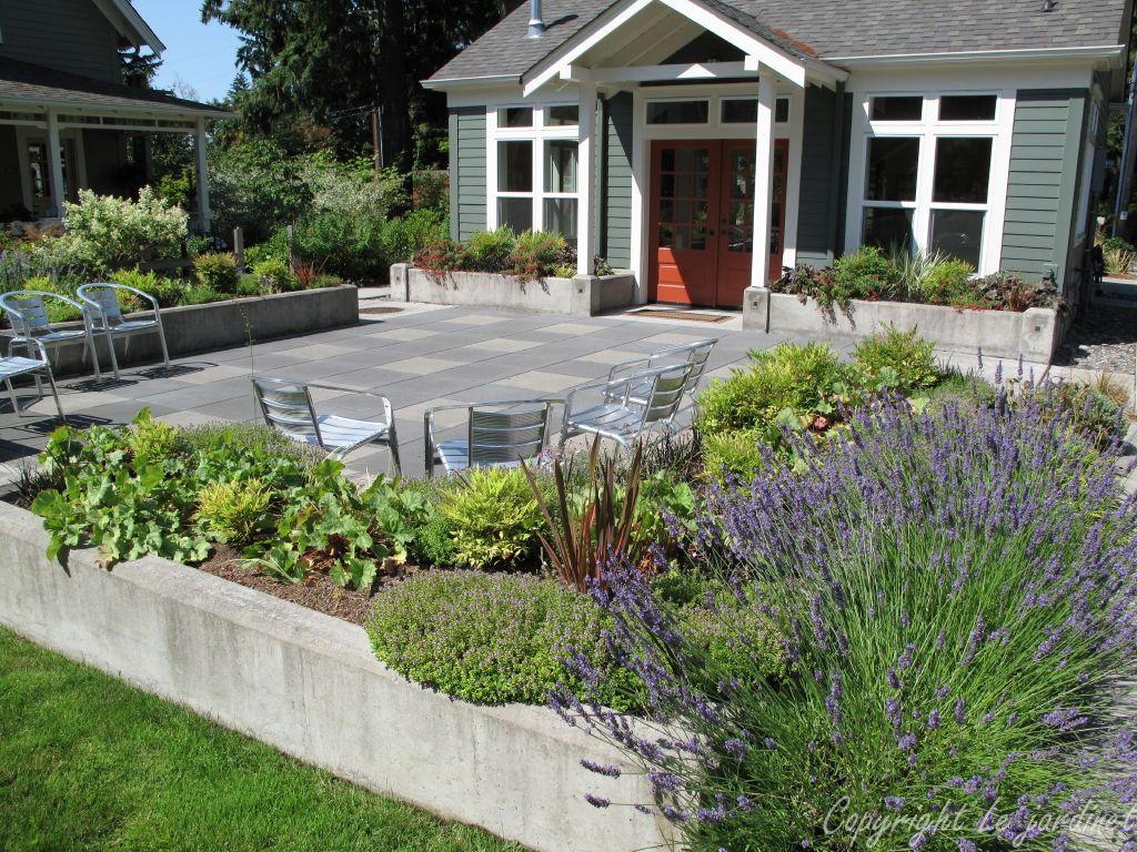 a simple raised border around this concrete paver patio creates a