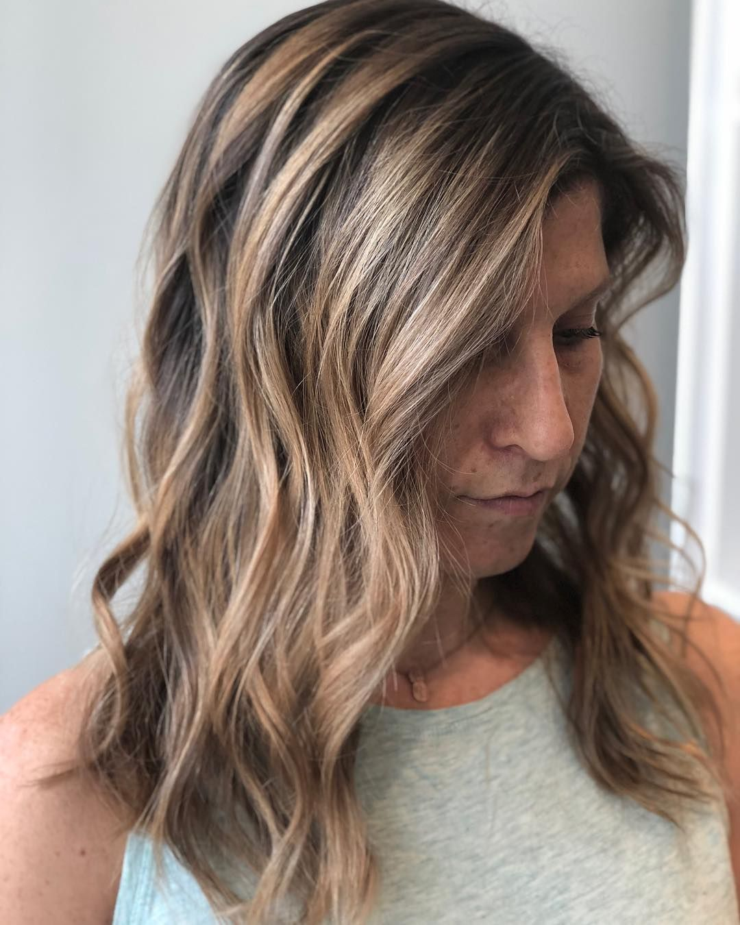 Hazelnut blonde balayage with loose waves by Beth Dassing