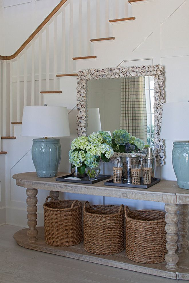 Coastal Foyer With Natural Elements This Features Wainscoted Staircase An Oval Console Table Filled Three Round Woven Baskets And