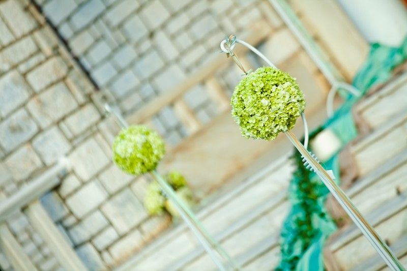 Metal stand with hanging hydrangea balls with ribbons.