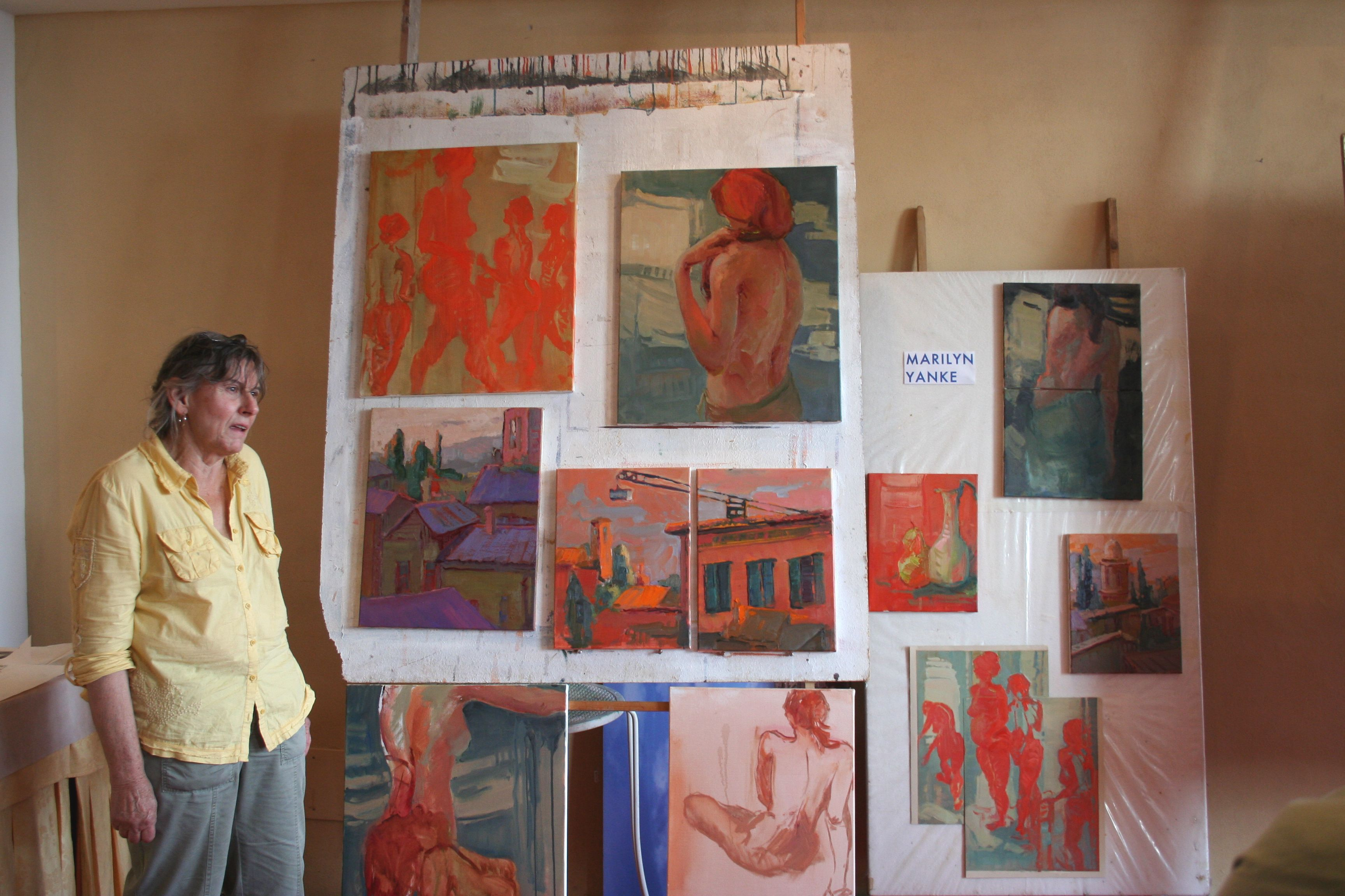 A full wall of Marilyn Yanke's expressive oil paintings inspired by Assisi, Italy