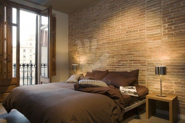 Modern brown bedroom with bare brick wall and full-length window