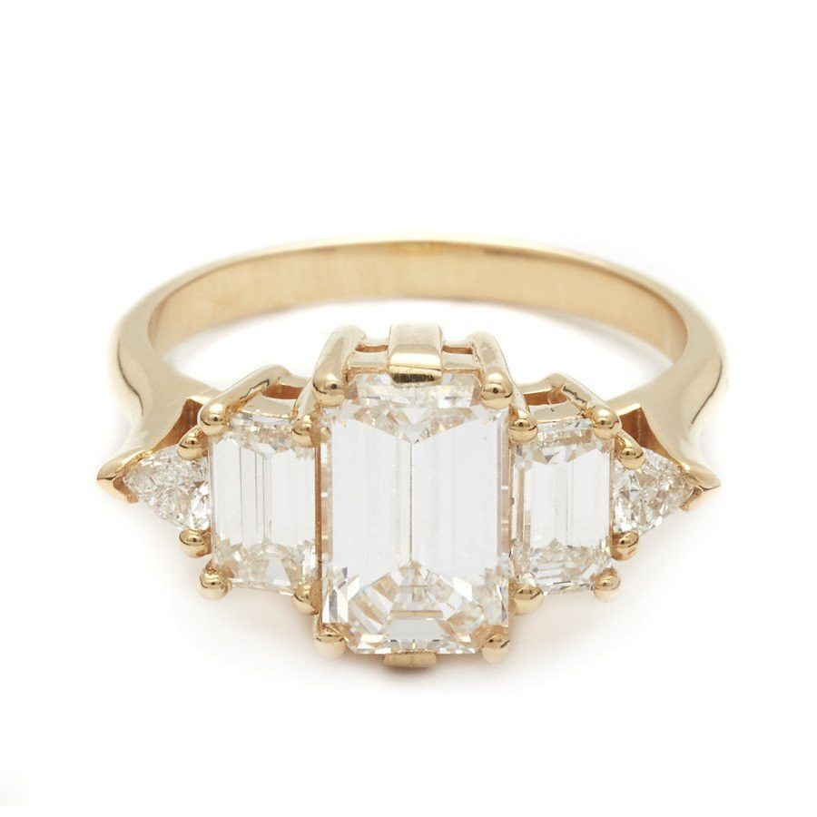 While the more unusual cuts of diamonds have been gathering momentum - Bea Three Stone Ring In Yellow Gold With A Emerald Cut White Diamond Centre Stone And Two Inverted Set Trillion Cut Diamonds From Anna Sheffield