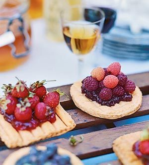 Puff pastry rounds are topped with fruit jam to make these sweet appetizers. Set out bowls of cheese and honey to let guests finish them off as they please.