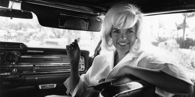 Vera Jane Palmer (1933 - 1967) better known as Jayne Mansfield, an American actress, in the passenger seat of a limousine. (Photo by Express Newspapers/Getty Images)