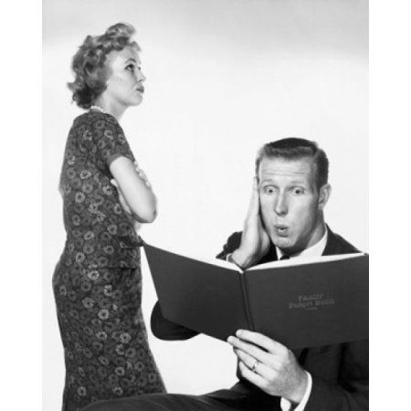 Close-up of a young man looking surprised while reading a budget book and a young woman standing beside him Canvas Art - (24 x 36)