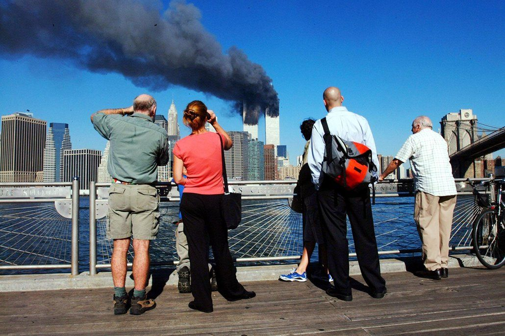 Pedestrians on the waterfront in Brooklyn, New York, look across the East River to the burning World Trade Center towers on September 11, 2001 after a terrorist attack.