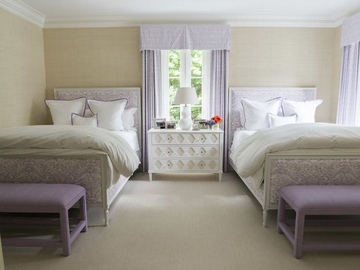 Lovely shared bedroom features walls clad in wheat grasscloth lined with twin beds upholstered in purple damask fabric and dressed in white and purple bedding flanking a shared nightstand, white arabesque chest, topped with white double gourd lamp situated under window covered in purple pleated valance with matching curtains alongside purple benches placed at the foot of the bed.