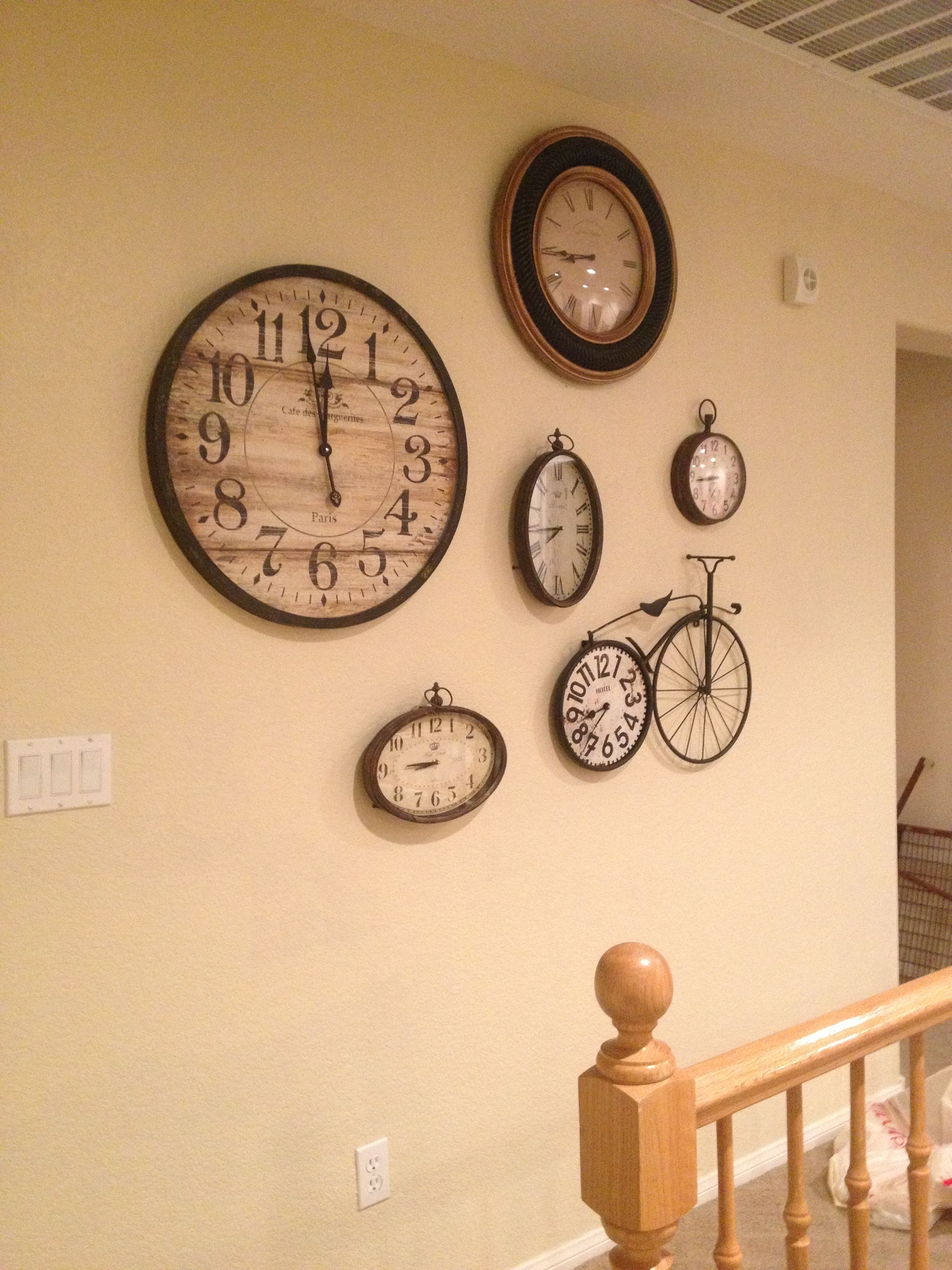 A collage of vintage clocks on a big empty wall. It\'s different but ...
