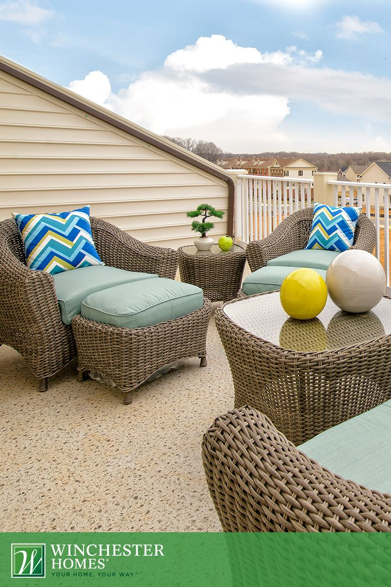 Wicker chairs and ottomans with neutral cushions and bright