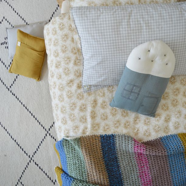 Spot floral golden duvet cover, check pillow caes, crochet wool blanket and teal house cushion all by Camomile London
