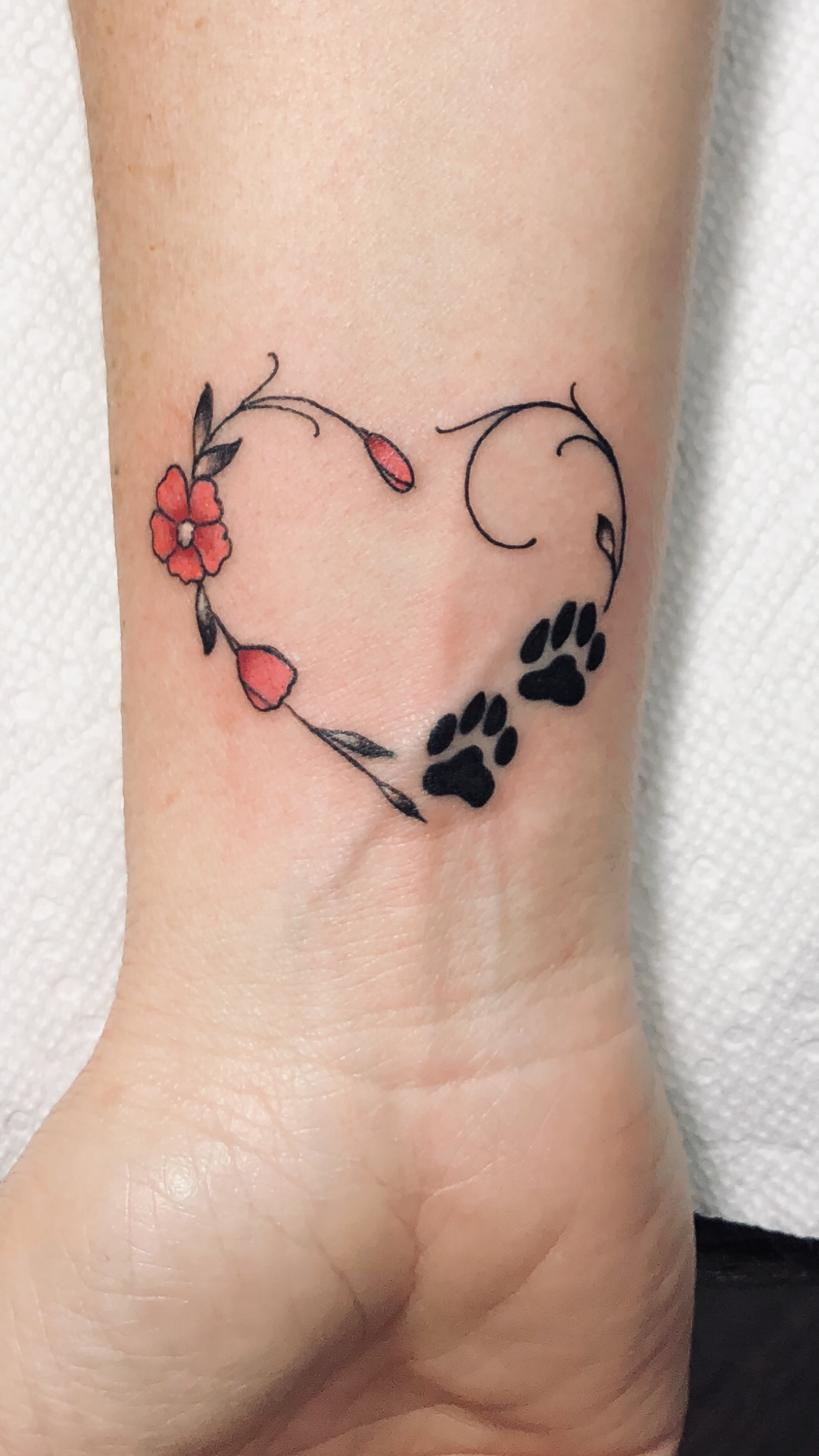 Heart with flowers and dog paw prints tattoo done by inkhouse 203