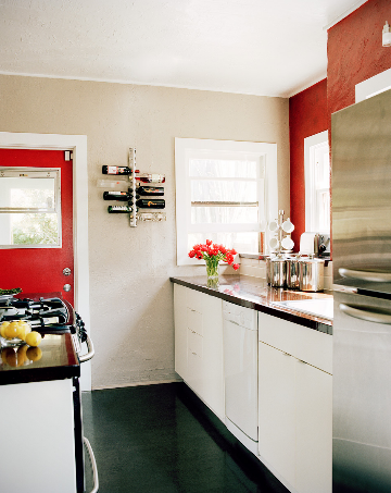small kitchen white cabinets red door accent wall black floor