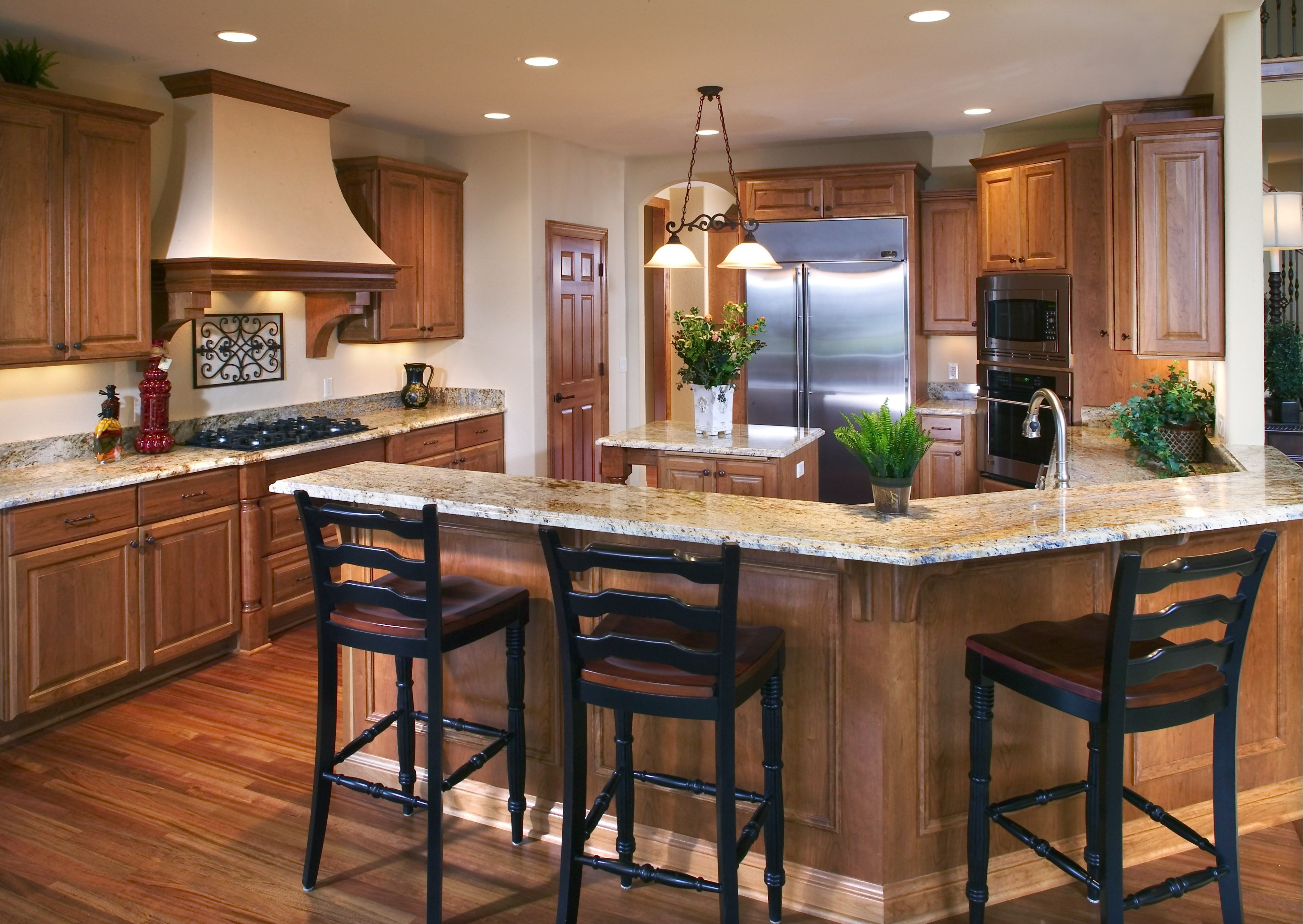 This kitchen features staggered cabinet heights, a granite ...
