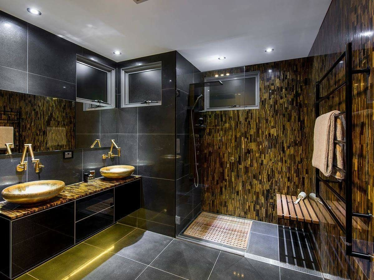 Tigers Eye walls & counters from Omicron Granite & Tile create a beautiful warm glow in this modern black bathroom: http://bit.ly/2n1c9bw