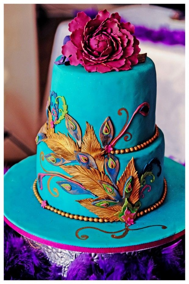 teal peacock cake with plum, gold, and green detailing. Fantastic use of feathers to offer color pops without overdoing it. And of course the plum sugar flower bouquet on top!