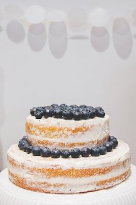 Lemon naked cake with lemon curd filling, buttercream frosting, and blueberry garnish.