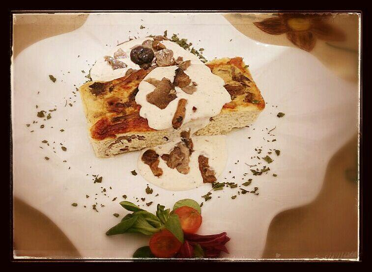 Pastel de setas silvestres con salsa de queso parmesano.