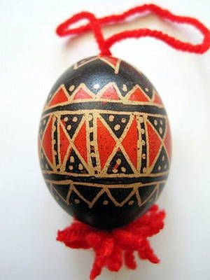 The red and black geometric patterns on this Slovenian Easter egg (pisanica) have been applied using a linear batik method. The outlines of the shapes are the egg's original color (brown) showing through. This area was covered with wax while the egg was dyed in both black and red dye to achieve the final result. Eggs like these come from the Bela Krajina region of Slovenia, in the southeastern part of the country.