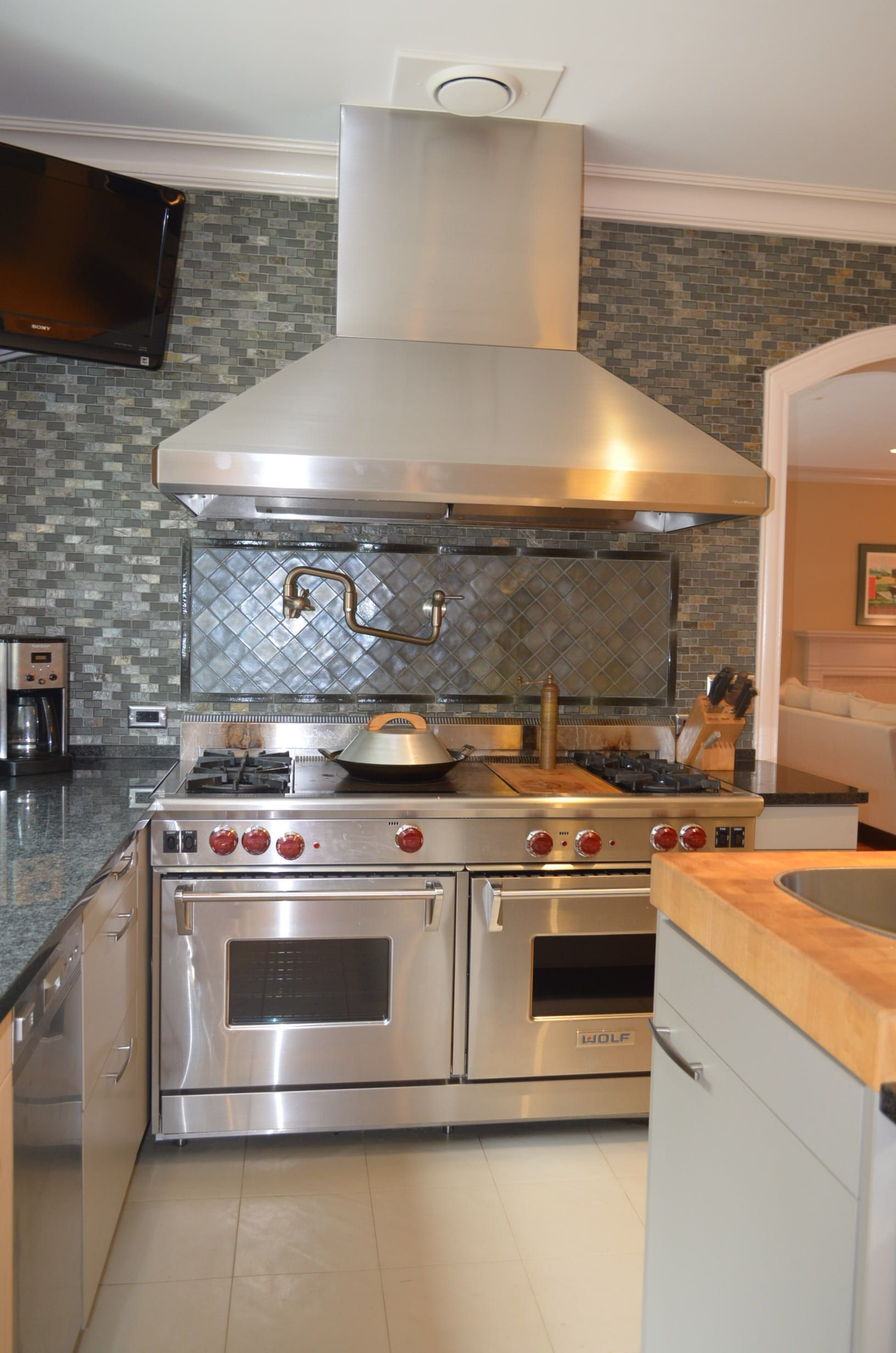 stunning glass tile backsplash with oversized hood vent and