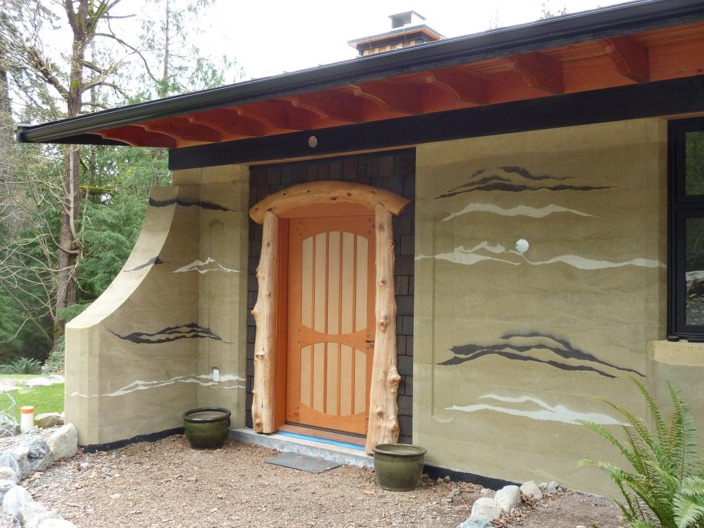 Fir and Maple front door with log surround on rammed earth house