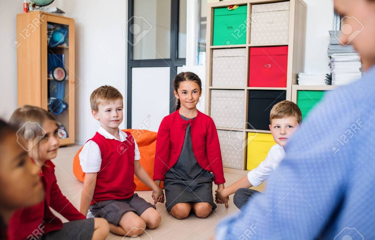 A Group Of Small School Kids With Teacher Sitting On The Floor In Class Holding Hands Stock Photo Affiliate Kids Teacher Sitt Kids School Photo Kids