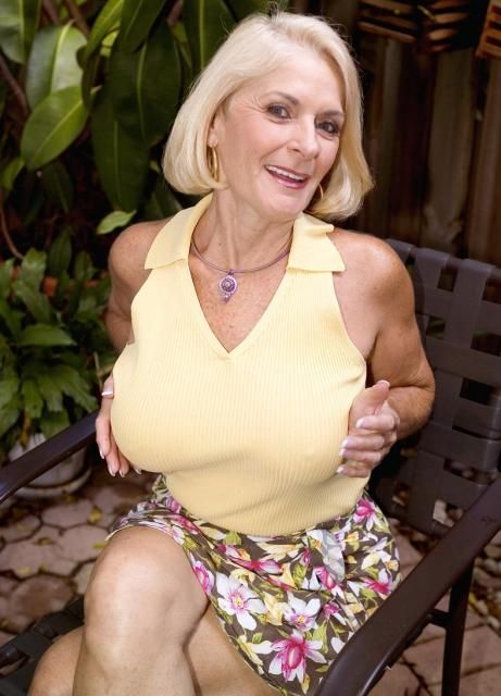 Busty Mature Blonde Holds Her Big Boobs In A Tight Yellow Sweater And A Flowered Print Skirt