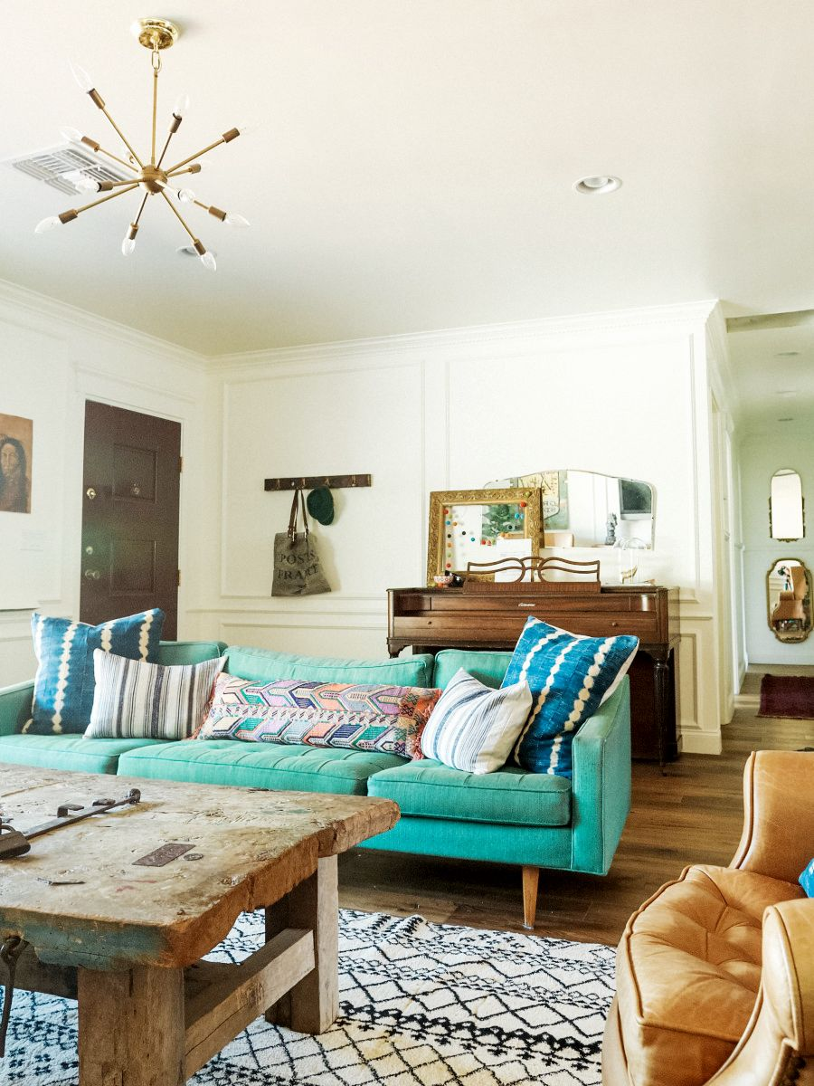 Vibrant green sofa with blue and patterned pillows, small Sputnik light fixture, salvaged wood coffee table, black and white rug