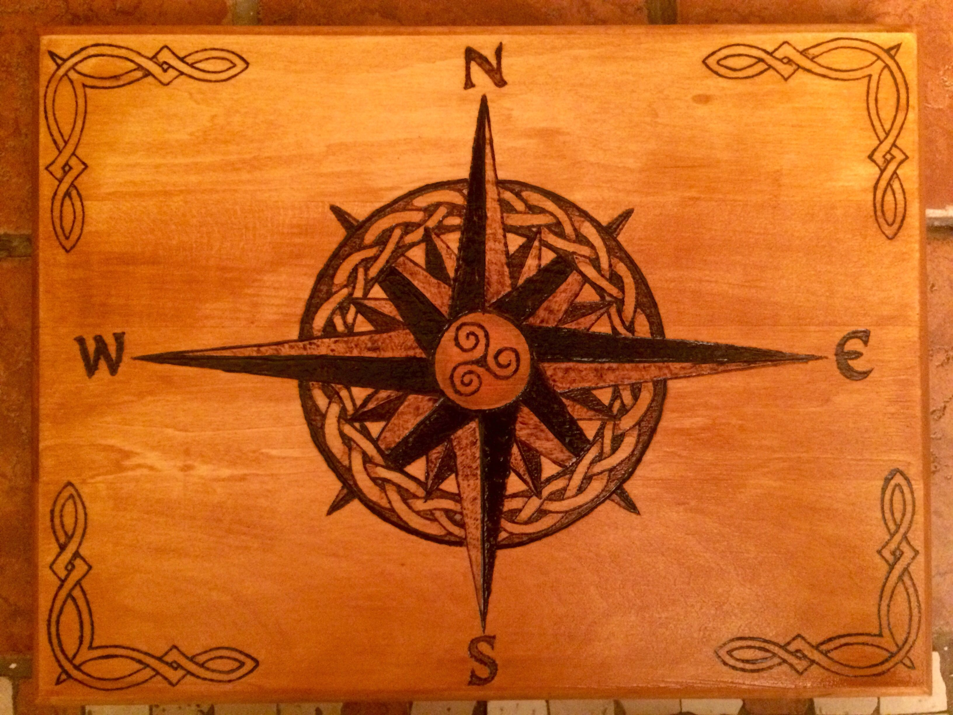 Wood burning compass rose with a celtic solomon knot weave around the center with celtic knot embellishments at the corners