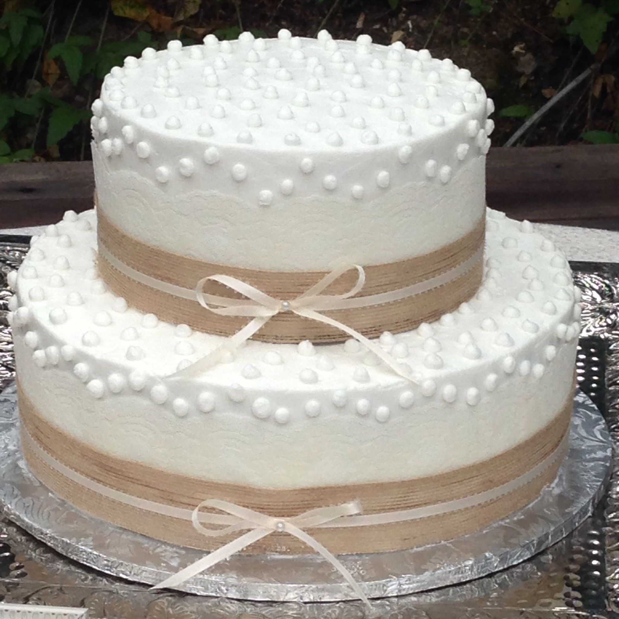 Rustic buttercream frosted wedding cake with lace and