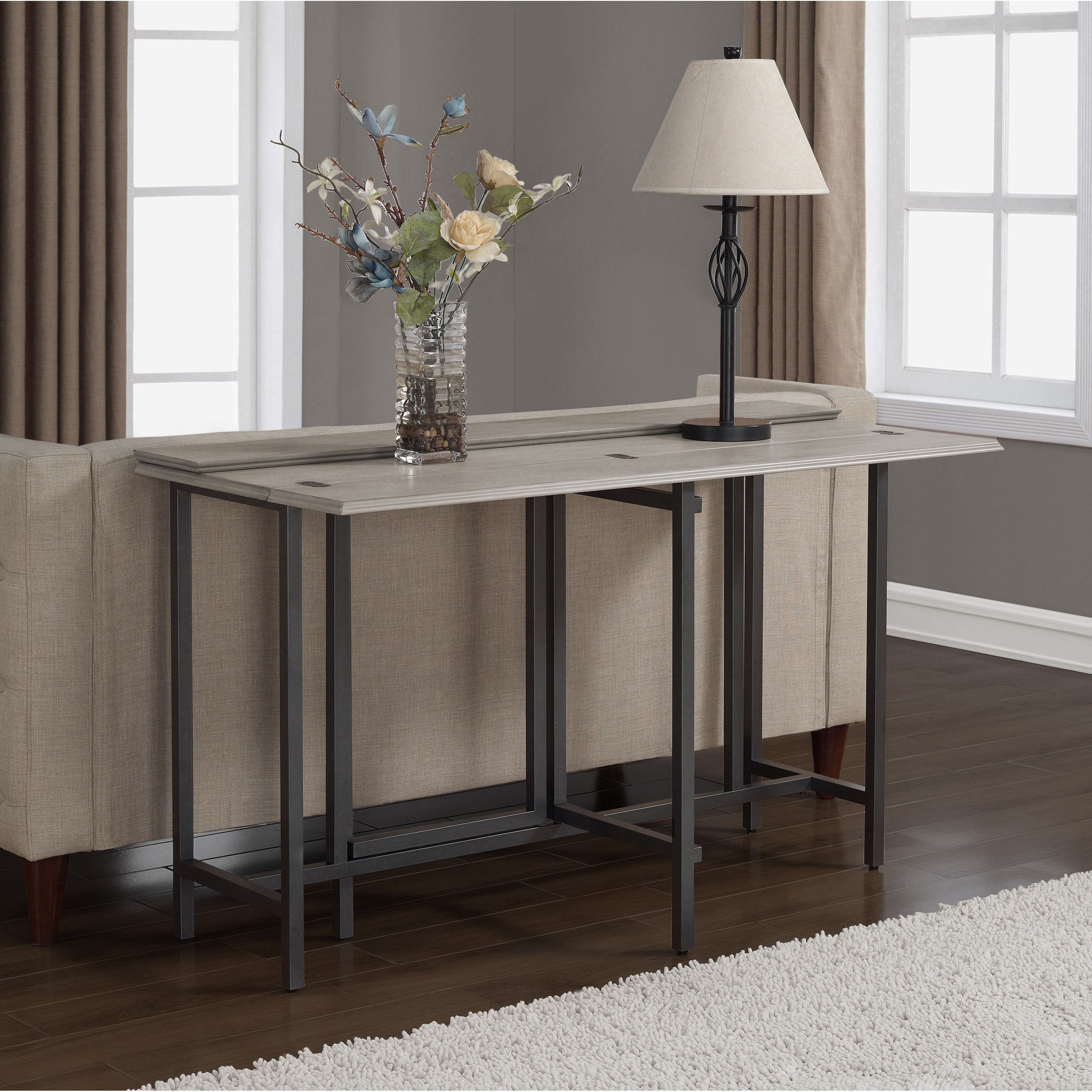This expandable sofa table with its clean lines and fresh look is an updated version of the old gateleg tables its beautiful grey top unfolds to go from