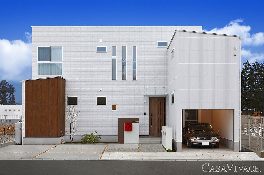 白いキューブ型の外観で書斎とインナーガレージのあるモダンな家