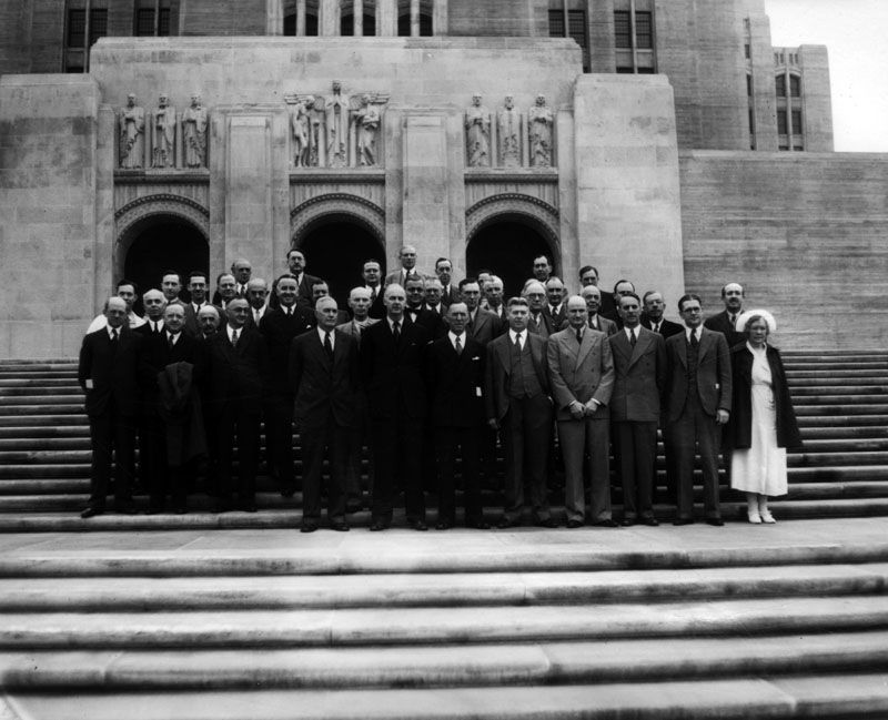 A Nurse And A Group Of Men Possibly Physicians Or Hospital Administrators Stand Together Outside Of Vintage Los Angeles Boyle Heights Hospital Administration