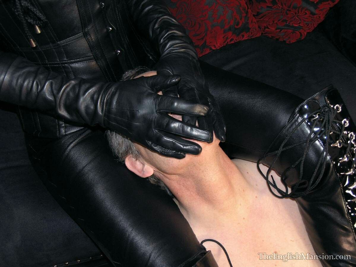 Dominatrix in full leather is smothering slave with gloves ...