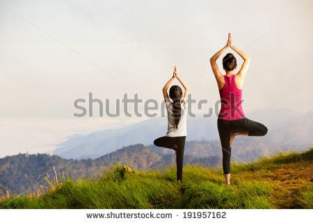 mother and daughter doing yoga tree pose at top of
