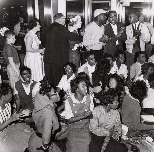 """White patrons walked behind """"sit and squat"""" demonstrators on April 24, 1961, at the Blue Boar cafeteria which refused to serve blacks. The cafeteria had unknowingly served four """"light-skinned Negroes"""" the same day, according to The Courier-Journal. (Courier-Journal file photo)"""