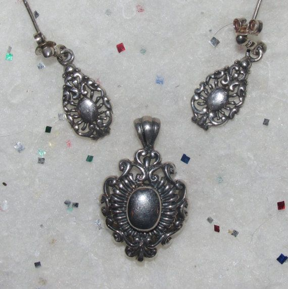 "This pendant and post earring set is made with a heavy .925 Sterling Silver and is marked as such. The center is a solid Oval with heavy filigree that has lots of swirls, lines and a heart at the top. The Pendant measures 1.25"" long x .75"" wide and the Earrings measure 1.2"" long x .4"