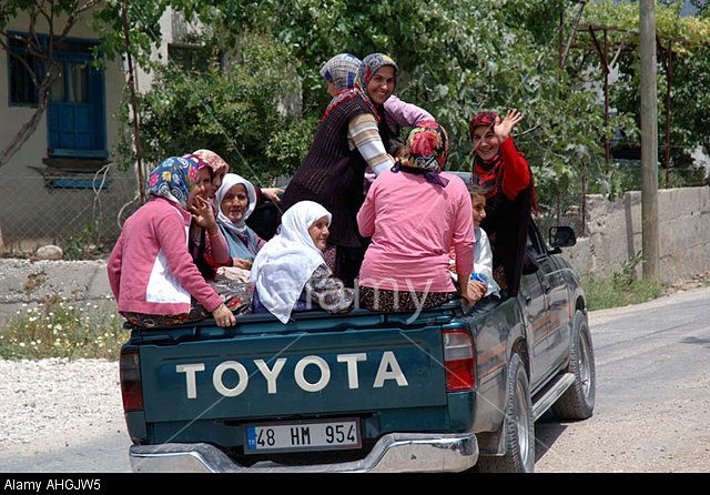 Women and children in pick-up truck being delivered home in small Turkish village in Southern Turkey. Stock Photo