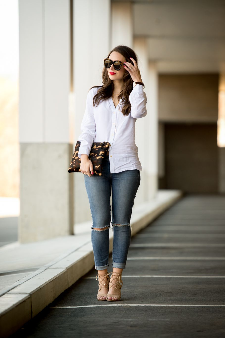 5dc456f012 Accessorizing a classic white shirt and blue jeans look with a camp clutch  and red lip for a chic effect