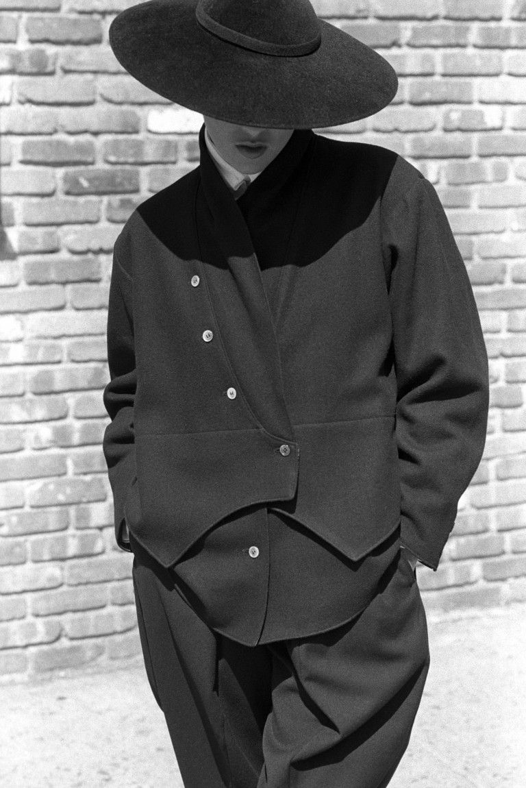 4a7176d93aa Model wearing a split-level jacket and matching black wool contoured and  cropped pants from the Yohji Yamamoto fall 1981 ready to wear collection.