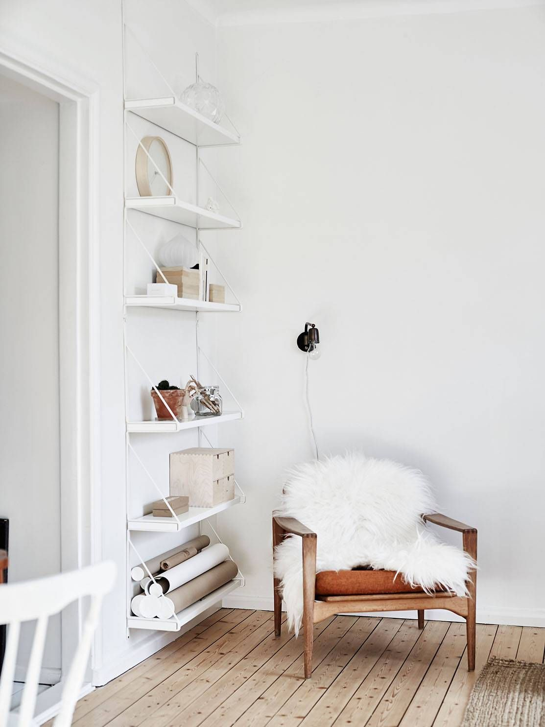 a beautiful corner - white walls, sheepskin and simple shelving
