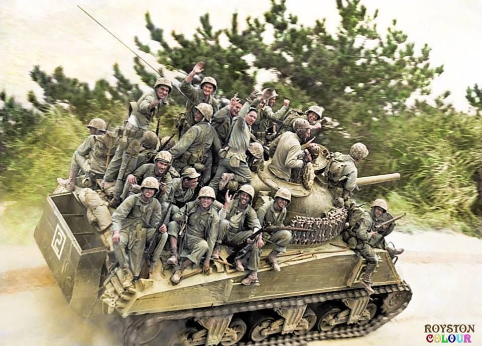 Grinning troops of the 29th US Marine Regiment, 6th US Marine Division, hitch a ride on board an M4A3 Sherman 105mm of Company A, 6th Tank Battalion, heading for Chuda in the drive towards Motobu Peninsula, Okinawa. April 5th 1945.   (Nb. the partially dismantled deep wading gear to allow the M4A3 to move through deep water during the landings a few days before.)