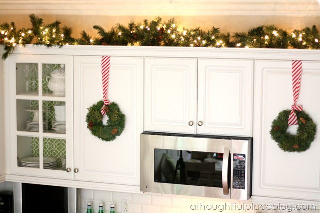 Lights And Greenery Above The Kitchen Cabinets Wreaths Hanging From Pretty Ribbon On The