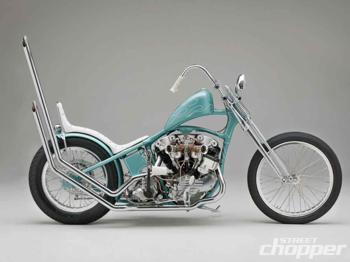 Light blue knucklehead hardtail custom with white seat, huge upswept pipes and springer frontend