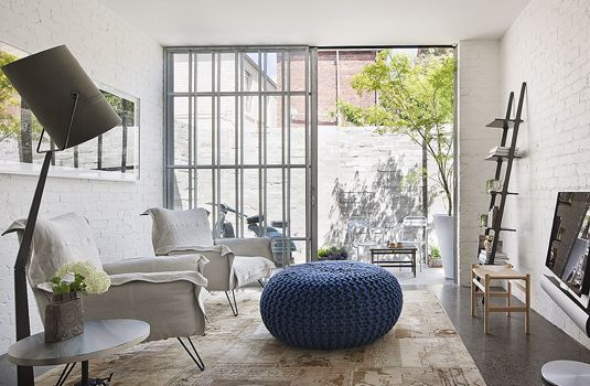 Love the painted brick, exposed ag concrete floors, and knited ottoman to soften.. Hecker Guthrie
